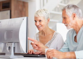 Elderly man assisting wife to learn computers