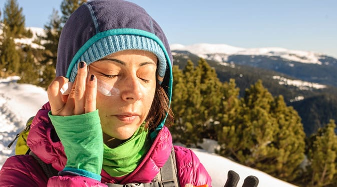 woman applying sunscreen in winter