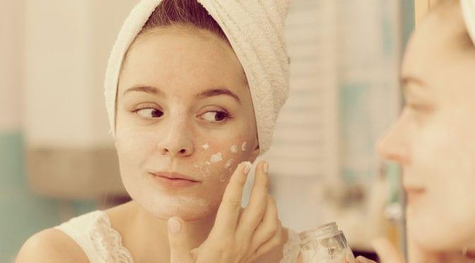 woman applying face cream in mirror