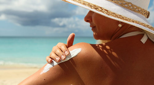 woman in hat applying sunscreen to shoulder